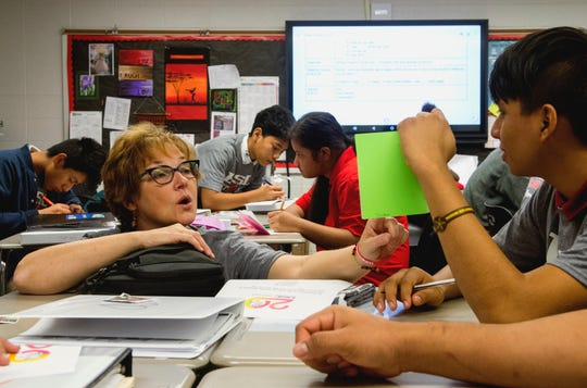 Harrison High School ESL teacher Janelle Nisly, left, goes over an assignment with Sophomore Jonathan Kanter Merida, right, from Mexico during an early morning English as a New Language  class Friday, Oct. 25, 2019. The assignment is to write stories that they will read to Stockwell Elementary School students.