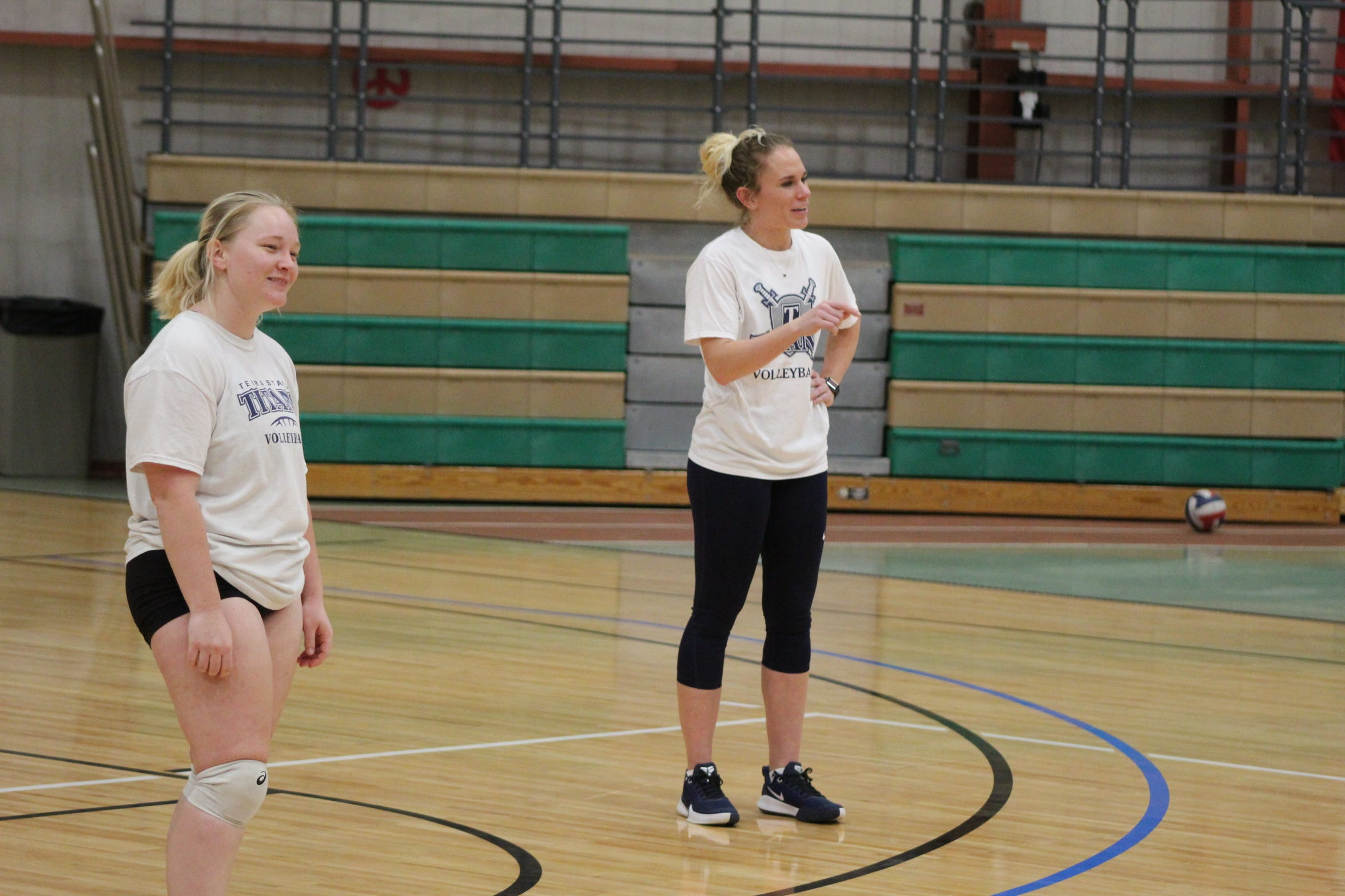 Terra State Volleyball Head Coach Stephanie Champine, pictured center, talks to players as freshman Megan Evans waits to return a serve during an Oct. 18 practice at the college's Student Activities Center.