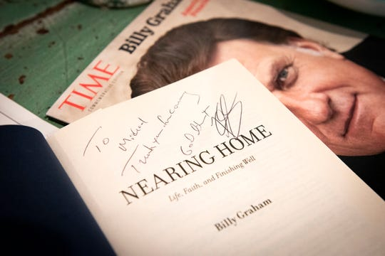 A signed book by Billy Graham sits on a shelf inside Michael Cogdill's living room.