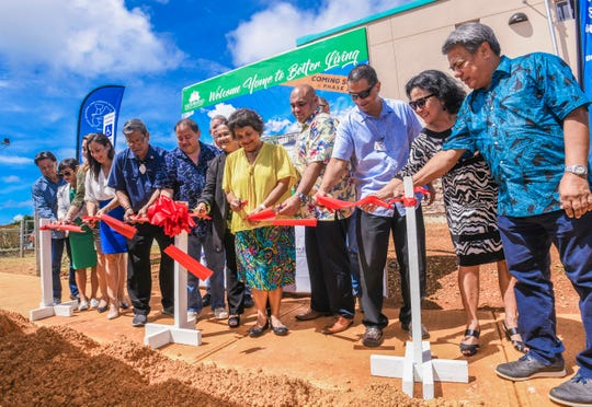 Gov. Lou Leon Guerrero, in yellow, and others cut a ribbon to celebrate the completion of 50 residential units for Phase I of the Ironwood Villa Del Mar housing project in Toto on Friday, Oct. 25, 2019. A ceremonial groundbreaking was also held moments earlier to mark Phase II, which will add another 88 units, said Carlos Camacho, Ironwood Guam Development vice president.