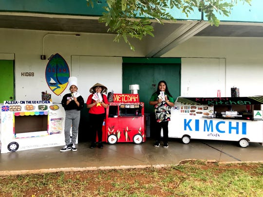 Winners of the United Nations day large cardboard food truck competition. First place Aliciyah Torres (Vietciyah), second Place ElizaEmma Evangelista (Kimchi Kitchen) and third place Alexa Hoya (Alexa's on the go kitchen) under Gate Teacher Raffy Manejero.