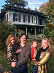 The Karr family, Justin, Guilaine and their daughters, Lulu, 6 and Pippin, 3 outside of Biggs House in Trumansburg. The house will receive a historical designation Nov. 16.