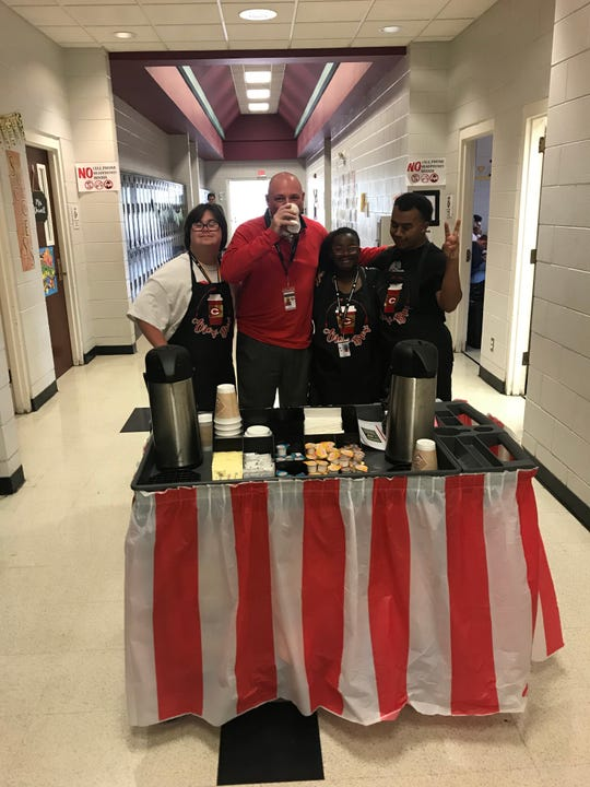 Life Skills students at Clinton High School serve Arrow Brew coffee to faculty member Clay Norton. Students pictured are, from left, Skylar Lepard, Raven Gibson and Taylor Hunt.