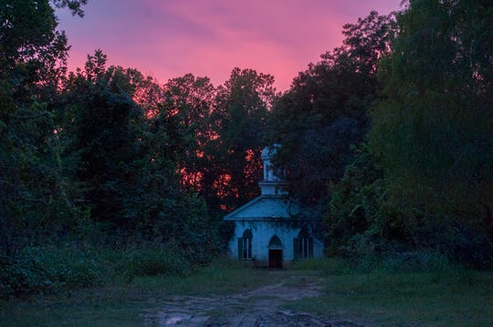 The Greater Mt. Zion Church in Rodney, Miss. sinks into the shadows of a sky painted by the colors of a setting sun Thursday, Oct. 17, 2019. The mysteries of Rodney succumb to darkness once more.