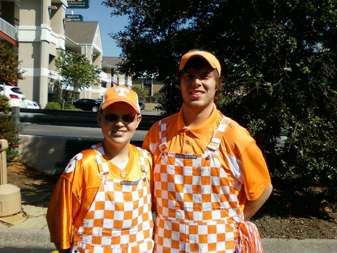 Jay Rogers and his brother, Daniel, stop for a picture before a Tennessee football game in Knoxville.