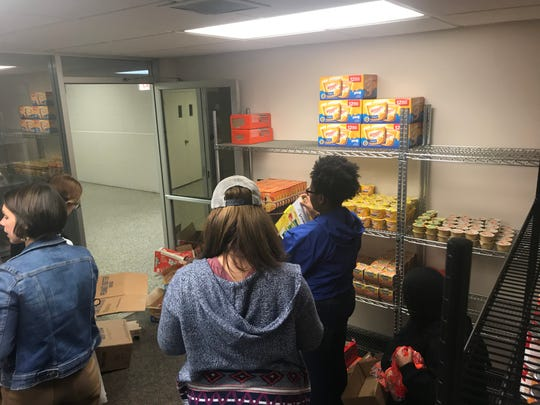 Students from the Inter-Club Council at the University of Memphis Lambuth Campus help stock the shelves at the food pantry.