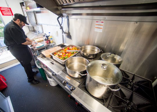 Chef Derek Cobble of Cobble Catering prepares food inside Dale Akins' new mobile commercial kitchen on Thursday, October 24, 2019.