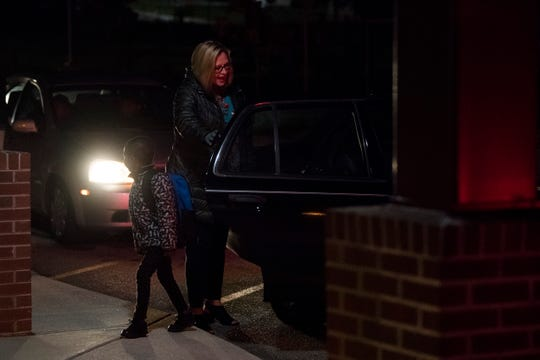 Tonya Cash, assistant principal at Christenberry Elementary, helps students in from the car line at Christenberry Elementary on Oct. 25. Cash's daughter Zoey transferred outside her school zone to attend the same school as her mom.