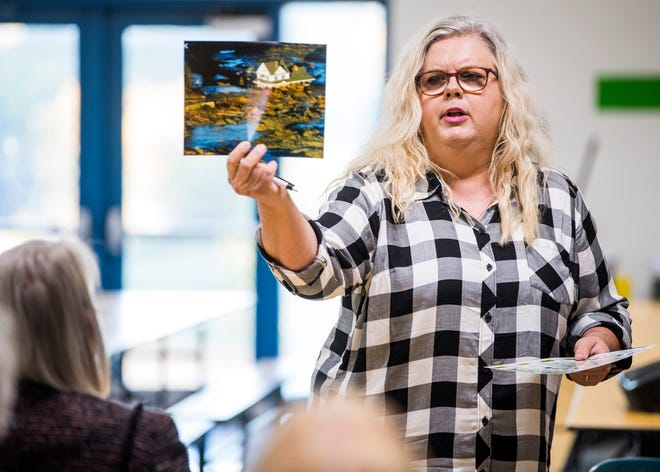 Julie Bledsoe shows the audience a photo of the Kingston coal ash spill during a public meeting held at Claxton Elementary School on Thursday, October 24, 2019.