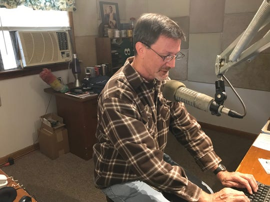 WLRY FM general manager Mike Lamneck works the airwaves during a recent morning show.