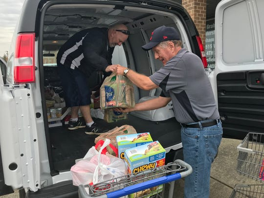 Rick Finnerty, an employee at Graham's Automall, helps unload a van load of donations of non-perishable food with volunteer Tom Brennan at the Make A Difference Day food drive, which continues Saturday.