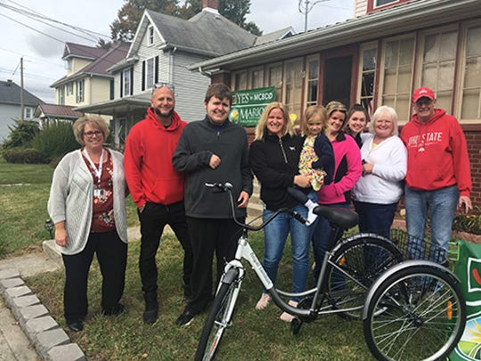 Jude Phillips, third from left, is one of 800 Marion County residents who receive services from the Marion County Board of Developmental Disabilities (MCDD). He recently received an adaptive bicycle from one of MCDD's partner agencies, Basinger Life Enhancement Support Services LLC, owned by Bobby Basinger, second from left. Jude stands next to his mother, Emily, and other supporters. MCDD has placed a levy on the ballot for the Nov. 5 general election.