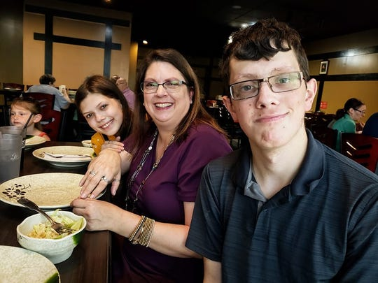 Connor Stevenson, right, enjoys a birthday lunch with his mother, Lori, center, and sister, Claire, at Iron Chef in Marion. Connor has been receiving services from the Marion County Board of Developmental Disabilities since he was an infant.