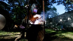 """Gary Spight welds pieces of an old water tank together to make a barbecue grill, a present for his sister """"Ta Ta."""" Spight grew up in La Grange, Tenn., at the home of his grandmother Margaret Beasley."""