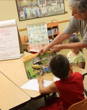 A volunteer presents a program about snakes to children at a Baxter County Library series last summer. Other programs included bird beak shapes, butterflies and trees