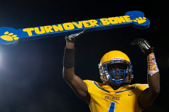 "Cedric Woods hoists Carroll's ""turnover bone"" in a 29-8 win over Wossman on Friday night at Thomas-Blade Memorial Stadium. Woods intercepted two passes, returning one for a 73-yard touchdown and made a 54-yard touchdown reception"