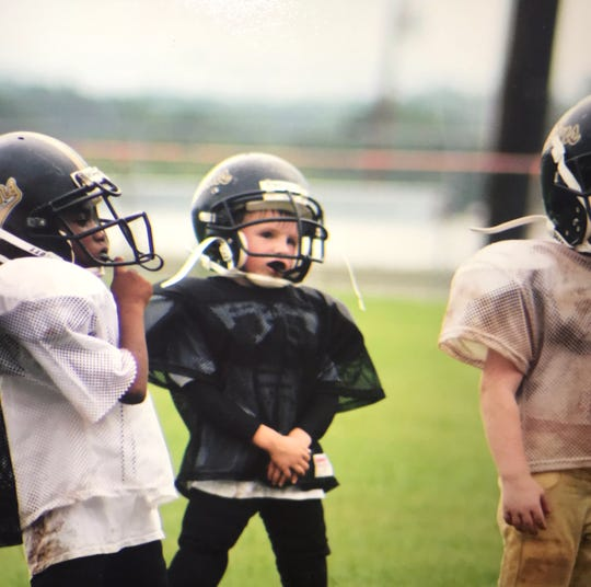 "Colton ""Bubba"" Addams stands and observes at a youth football practice."