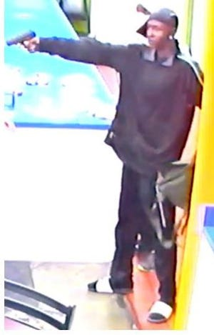 The unidentified robber was caught on video brandishing a black handgun as he entered the business.