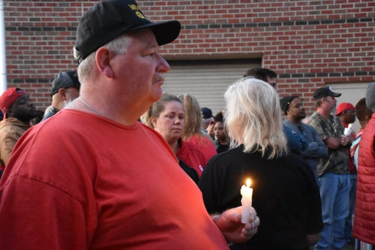 Gregory Bayne listens to the opening prayer at a candlelight vigil on Thursday.
