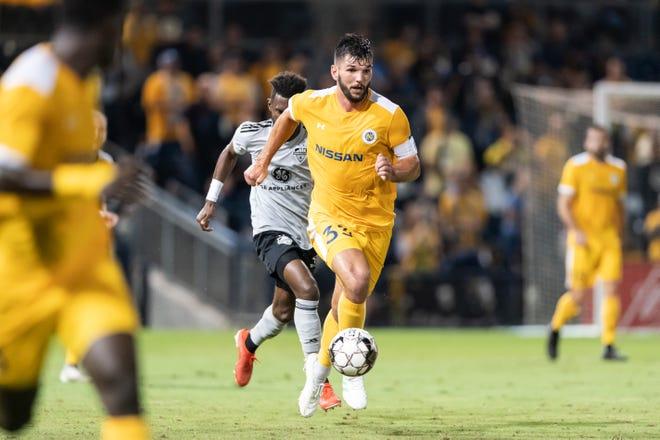 Nashville SC center back Forrest Lasso eludes Louisville City defender, dribbling up field at First Tennessee Park. Oct. 8, 2019.