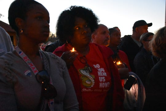 Lakeya Patterson, left, and Bobbi Sanders, listen to speakers at a candlelight vigil in memory of Roy McCombs on Thursday.
