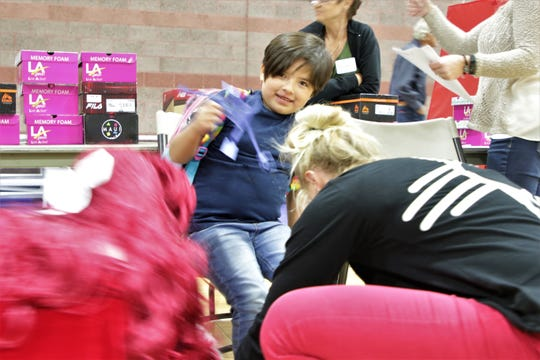 A kid receives new, free shoes, Thursday, Oct. 24, 2019, during the Farmington Rio del Sol Kiwanis Shoes for Kids event at the Boys & Girls Club of Farmington.