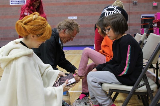 A volunteer from the Four Corners Ichigo cosplay group fits a kid for a new, free shoe, Thursday, Oct. 24, 2019, at the Farmington Rio del Sol Kiwanis Shoes for Kids event at the Boys & Girls Club of Farmington.