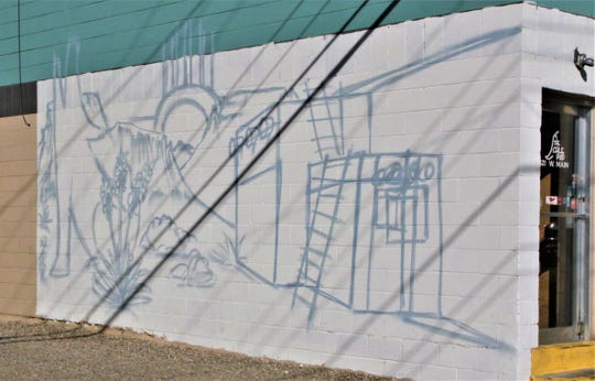 The outline of a Luke Paul Art in the Alley mural adorns the west side of the building that houses the Chile Pod restaurant at 121 W. Main St. in downtown Farmington.