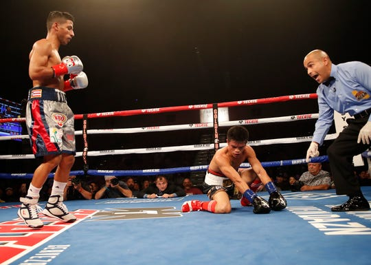 At right, Raymond Tabugon of the Philippines is sent to the ground by Puerto Rico's Angel Acosta at Fantasy Springs Casino on October 24, 2019. Acosta won by TKO in the 5th round.