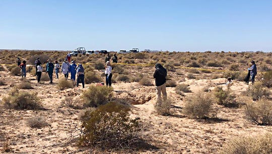 A group of women and Sonora investigators dig up a mass grave with 13 bodies near Rocky Point on Oct. 24, 2019, as federal police and National Guard soldiers look on.