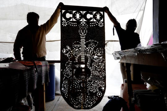 Fotografía fechada el 11 de octubre de 2019, que muestra a artesanos de papel picado trabajando en el municipio de Huixcolotla, en el estado de Puebla (México).