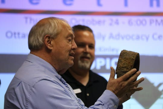 Jack Jones, chairman of Poggemeyer Design Group, and Port Clinton Mayor Mike Snider discuss the need for upgrades to the city's aging infrastructure with actual pieces of its waterline that illustrate the problem.