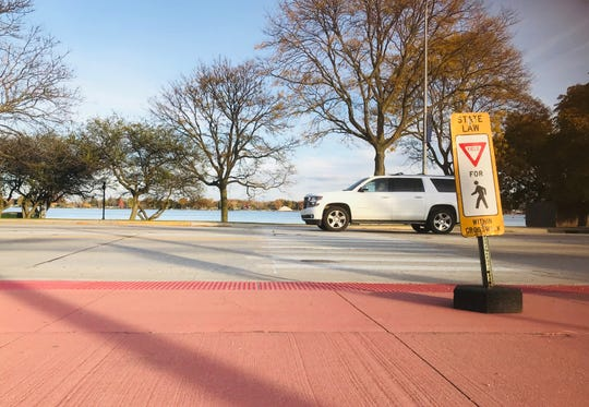 A car passes one of several crosswalks on Riverside Avenue Thursday, Oct. 24, 2019, in St. Clair. The crosswalks were repainted when the road diet restriping was done this summer. Some city officials had questions this week about jaywalking.
