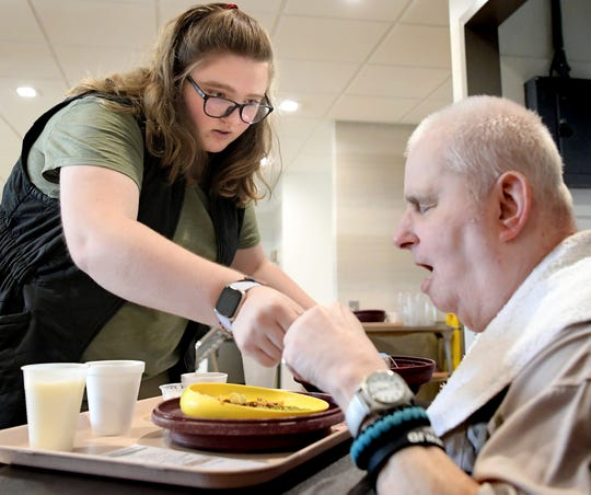 Pleasant Acres Nursing and Rehabilitation Center recreation therapist Britney Sager serves lunch to resident Curvin Ridley, formerly of Glen Rock, at the center Thursday, October 24, 2019. The facility was privatized when Premier Healthcare Management purchased it from York County in October of 2018. Bill Kalina photo