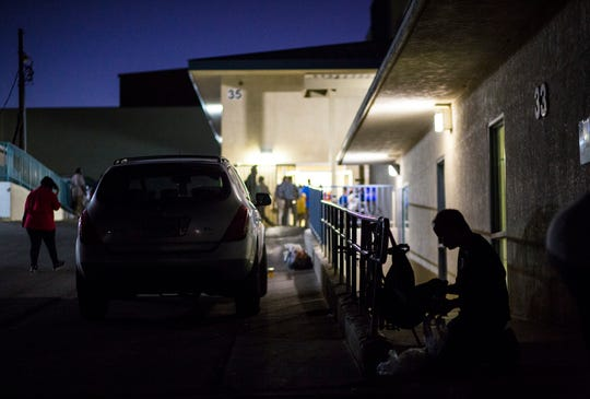 In this Tuesday, Oct. 15, 2019 photo, A patron of The Salvation Army homeless shelter, right, checks his belongings at the shelter near downtown Las Vegas.  Officials say they're trying to stem complaints and compel homeless people to seek help as part of a broader strategy to protect the homeless and the public, safeguard business interests and address a public health crisis. (Chase Stevens/Las Vegas Review-Journal via AP)