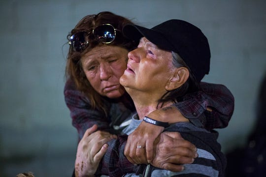 In this Tuesday, Oct. 15, 2019 photo, Alice Pate, left, comforts Kathleen Sutton as she talks about the struggles of living on the streets as they prepare to camp out for the night on Garces Avenue near Main Street in downtown Las Vegas. Officials say they're trying to stem complaints and compel homeless people to seek help as part of a broader strategy to protect the homeless and the public, safeguard business interests and address a public health crisis. (Chase Stevens/Las Vegas Review-Journal via AP)