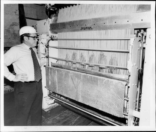 Joseph Gioia, vice president of Bravo Macaroni, watches as spaghetti comes out of a machine in 1977.
