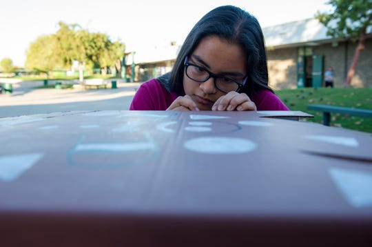 Alisal High School student adds her finsihing touches to a costume that will transform a kids wheelchair for Halloween on Friday, Oct. 25, 2019.