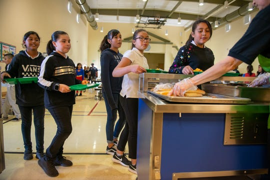 Students at the Monte Bella elementary school line up to get their bread sticks and chicken fajitas on Thursday, Oct. 24, 2019.
