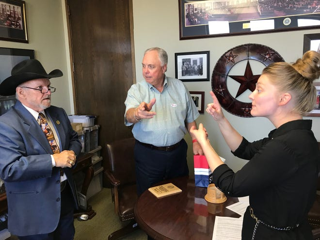 "Aulby ""Larry"" Gillett, left, communicates with State Representative Drew Darby, center, through American Sign Language interpreter Breanna Norman during a small ceremony to than the legislator for his help in passing legislation aimed at helping the deaf and hard-of-hearing."