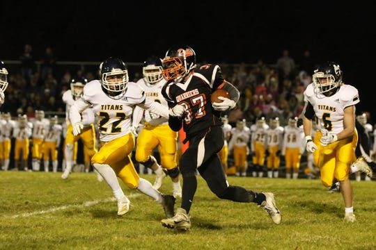 Logan Stone of Dell Rapids runs the ball past the defense by Kiet Gilberts of Tea Area during Friday night's game in Dell Rapids.