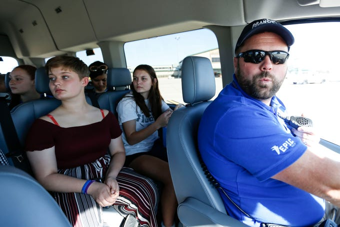 Hollister School students Makyla Lear (left), 15, and Chloey Donohew, 15, look out a van window driven by Jesse Fosnaugh, the deputy director of operations and Maintenance for the Branson Airport, during a tour of the Branson Airport runway and ramp on Wednesday, Oct. 23, 2019.