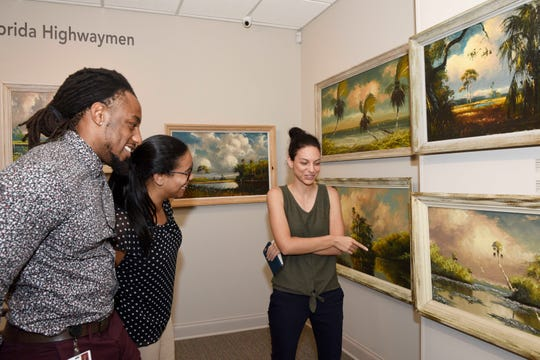 FSU College of Medicine students Allan Joseph, left, and Krista Gomes examine painting elements pointed out by Alyssa Allen at the Backus Museum in Fort Pierce.