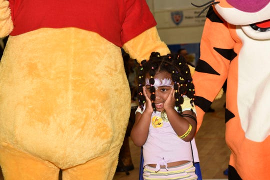 Kerstanne F., center, gets to meet Pooh and Tigger at St. Lucie County's Early Learning Coalition's KIDMania at Minsky Gym and Whispering Pines Park in Port St. Lucie.