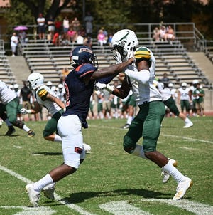 COS defensive back Bobby Peele, left, jams an opponent's receiver in a football game.