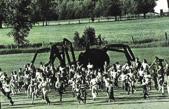 "A crowd of people sprint away from the giant spider in a scene from ""The Giant Spider Invasion,"" a movie shot in the Merrill and Gleason areas."