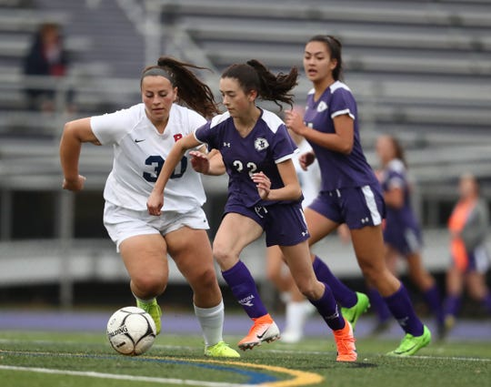 John Jay-Cross River's Julia Rossi (22) works the ball against Byram Hills' Alea Zaccagnino (30) during their 3-1 win in the first round of girls soccer playoffs at John Jay High School in Cross River on Friday, October 25, 2019.