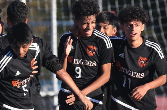 White Plains' Ruben Collazos (9) is all smiles as he is greeted by teammates after his goal against Scarsdale during boys soccer playoff action at White Plains High School Oct. 24, 2019. White Plains won the game 4-1 in PKs.