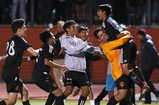 From right, White Plains' Eric Ramirez (5) jumps into the arms of teammates after his penalty kick sealed the 4-1 victory against Scarsdale during boys soccer playoff action at White Plains High School Oct. 24, 2019.
