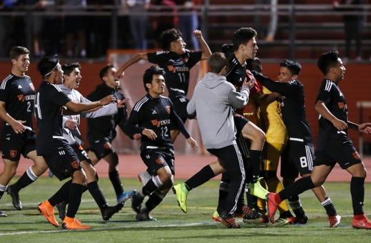 White Plains players storm the field after defeating Scarsdale 4-1 in penalty kicks  during boys soccer playoff action at White Plains High School Oct. 24, 2019.